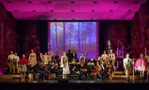 """Photo of """"Into The Woods"""" cast on stage with musicians"""