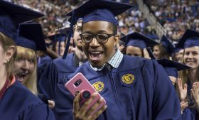A male graduate holds a phone and takes a photo during the May Commencement ceremony on May 12, 2017.