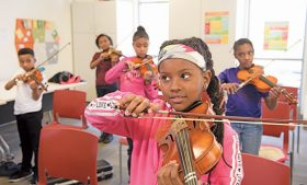 Photo of kids playing violins