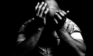 Photo of soldier with hands to his face