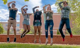 """Photo of students jumping and making the letter """"G"""" with their arms"""