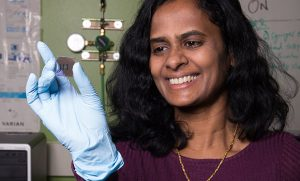 Picture of Dr. Hemali Rathnayake holding a prototype of a miniature solar cell.