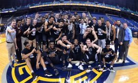 UNCG men's basketball team poses for a picture on the court