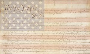 Image of Constitution document with American flag in the background