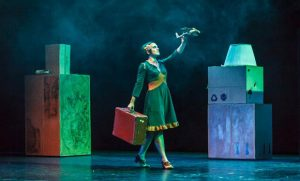 Photo of actress on stage holding suitcase, toy airplane