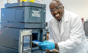 Joseph Mwangi loads samples into machine in lab.