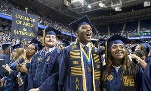 Photo of graduates smiling during commencement ceremony.