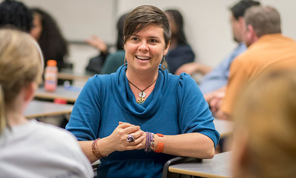 Photo of Dr. Powers talking with students in class.