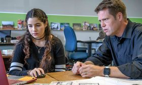 Photo of Jessica Ocasio and Travis Hicks working together at a laptop computer