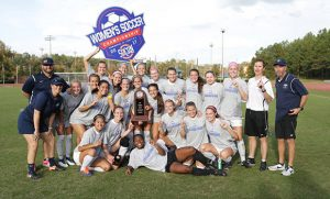Soccer team poses for picture with trophy