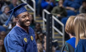 Commencement photo of graduate walking across stage