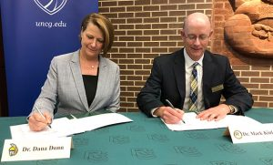 Dana Dunn and Mark Kinlaw signing documents