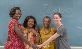 Group photo of women joining hands in front of chalkboard