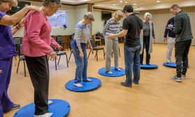 Photo of UNCG researchers observing Well-Spring residents on wobble boards.