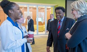 Photo of President Spellings and Chancellor Gilliam speak with a School of Nursing student Bianca Wade and Dr. Jacqueline DeBrew.