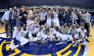 Team photo of men's basketball team with pieces of the net that was cut down