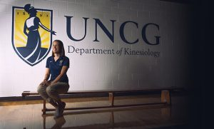 Portrait of Dr. Erin Reifsteck in gym with UNCG logo on wall behind her