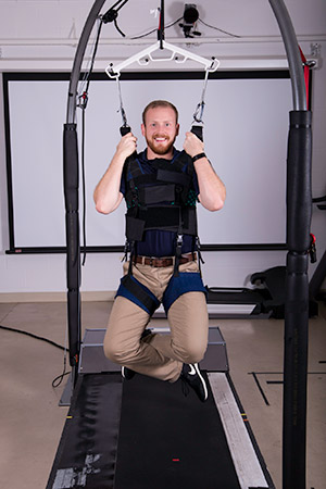 Photo of student Jason Moody wearing harness, hanging above treadmill that is used for trip-training.