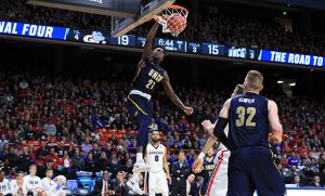UNCG Spartan Basketball player dunking the ball at the NCAA tournament 2018