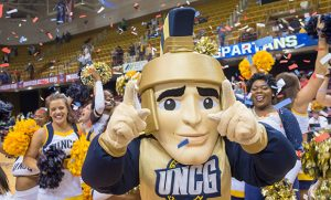 Photo of Spiro mascot and UNCG cheerleaders celebrating on court with confetti falling