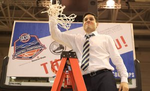 Photo of Wes Miller on ladder, celebrating after cutting down the net.