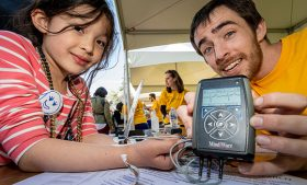 A child and volunteer pause to look at the camera while enjoying an activity during the Science Everywhere festival.