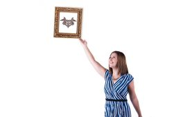 Photo of student reaching up to straighten out a picture frame