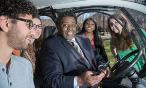Chancellor Gilliam in G-Whip golf cart with students.