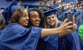 Three female graduates hold cell phones in front of them as they pose for a group photo at a May Commencement ceremony.