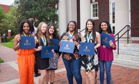 Students outside the UNCG auditorium wearing medallions hold certificates for the Leadership Challenge program.
