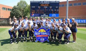 Photo of UNCG softball team with trophy and scoreboard after 2018 SoCon championship