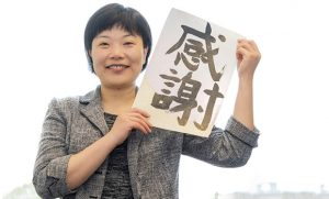 Portrait of Jane He holding paper with Chinese calligraphy