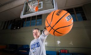 Photo of Dr. Tom Martinek holding basketball in gym