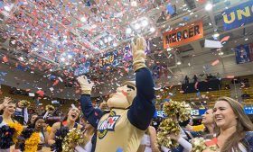 Photo of Spiro mascot and cheerleaders celebrating win with confetti on court