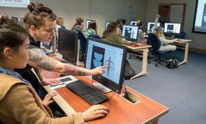 Photo of instructor pointing at student's computer screen of fashion design 3D software.