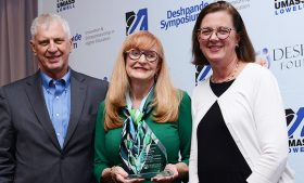 Photo of Dr. Dianne Welsh holding entrepreneurship award with representatives from UMass Lowell and the Deshpande symposium.