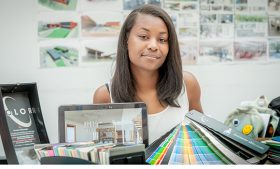 Photo of student looking at camera with paint samples in front of her.