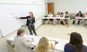 Dr. Emily Janke pointing at a white board in front of a small group of faculty and community members.