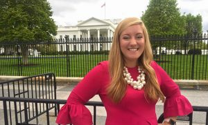 Photo of Brette Powell standing in front of The White House.