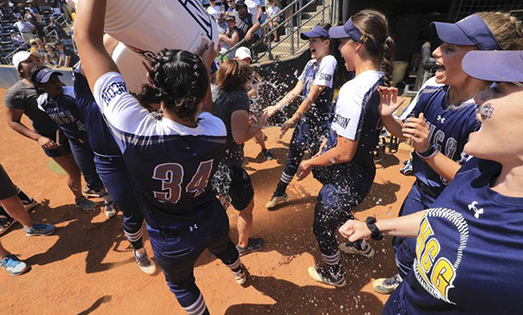 Softball players pour bucket of water on Janelle Breneman in posts-game celebration.