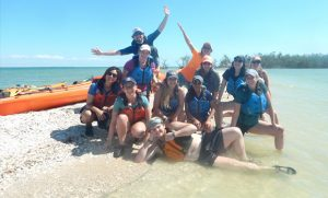 Group photo of students in clear water wearing life jackets with sea kayak behind them.