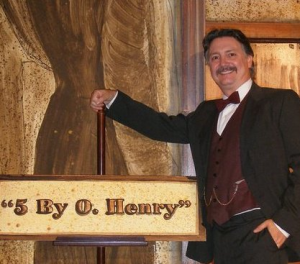 """Image of Stephen Hale dressed as O. Henry next to """"5 by O. Henry"""" sign"""
