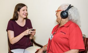 Young woman plays music for older woman wearing headphones.