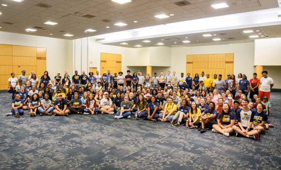 Group photo of student volunteers wearing blue and gold in EUC ballroom.