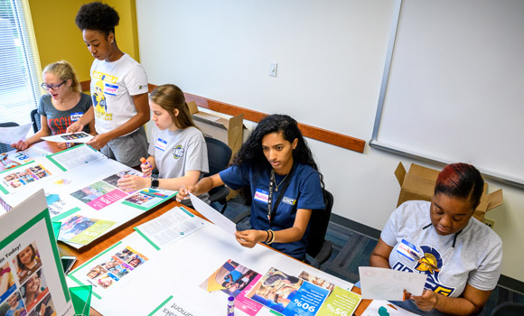 Students sitting at a table working on posters for the Girl Scouts.