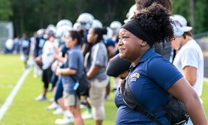 Photo of UNCG student on sidelines of football game