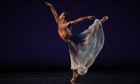 Photo of Mark Morris Dance Group member dancing on stage