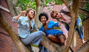 Photo of three people sitting in a tree