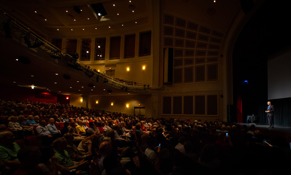 Photo of Alan Alda speaking to large crowed at UNCG Auditorium