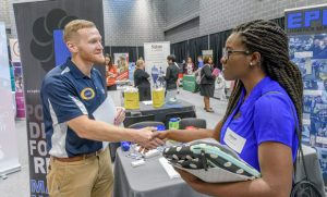 Alumnus shaking hand of student at the fall career fair.